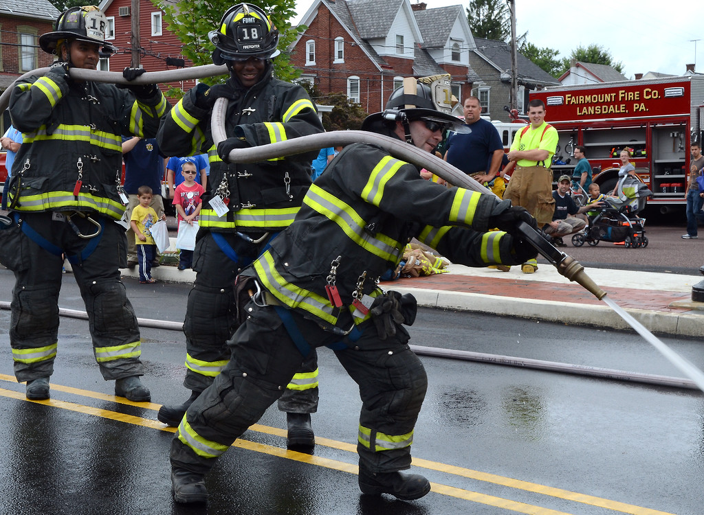 Description of . Fairmount Fire Company members participate in a water battle demonstration for the Fairmount Fire Company 125th Anniversary festivities during the Lansdale Founders Day celebration on Saturday August 23,2014. Photo by Mark C Psoras/The Reporter
