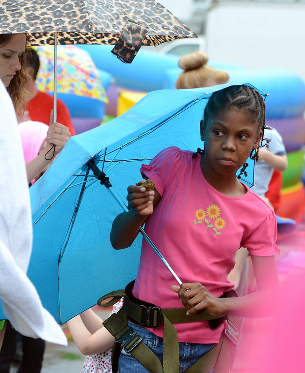 Description of . Sharon Smith ,10, holds an umbrella as rain falls during the Lansdale Founders Day celebration on Saturday August 23,2014. Photo by Mark C Psoras/The Reporter