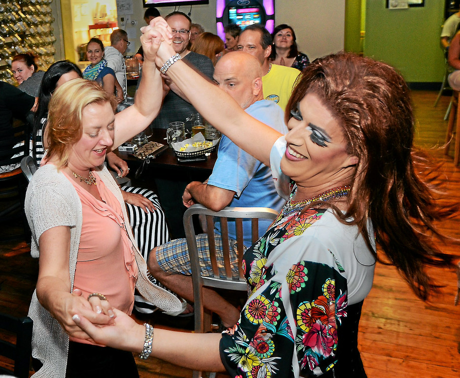 Description of . Katrina Escalarza dances with a patron during a show at Round Guys Brewing Co. in Lansdale on Saturday June 22, 2014. Photo by Mark C. Psoras/The Reporter