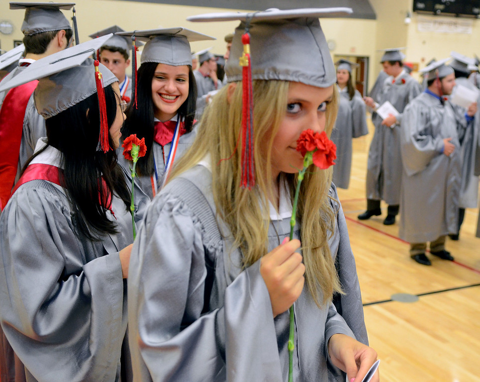 Description of . Upper Dublin High School Class of 2014 member Anna Trentini smells her carnation as the class  lines up in the gym before the start of  their Commencement Ceremony at the school on Tuesday evening June 10,2014. Photo by Mark C Psoras/The Reporter