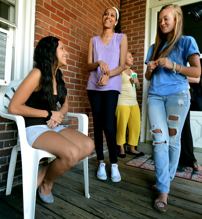 Description of . Incoming freshman Bianka Maradiaga, seated left, chats with Souderton Area High School juniors Cheyenne Scott, right, and Vishwa Patel, center, on her porch Wednesday, Aug. 6, 2014. The principal, administrators, teachers and students toured the district to welcome the new members of the freshman class. Montgomery Media photo by Bob Raines