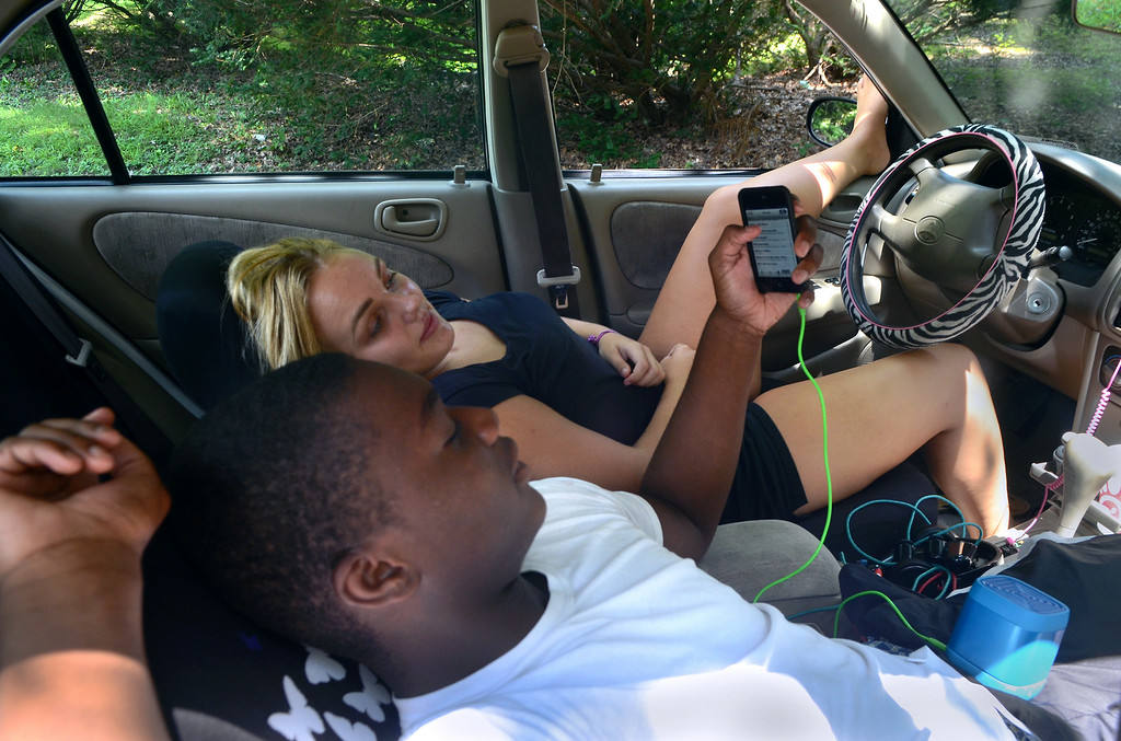 Description of . Cheltenham High School students Rachel Davis and Dave Pelzer kick back in her car parked at the Curtis Arboretum on a hot and sunny Tuesday afternoon August 5,2014. Photo by Mark C Psoras/The Reporter
