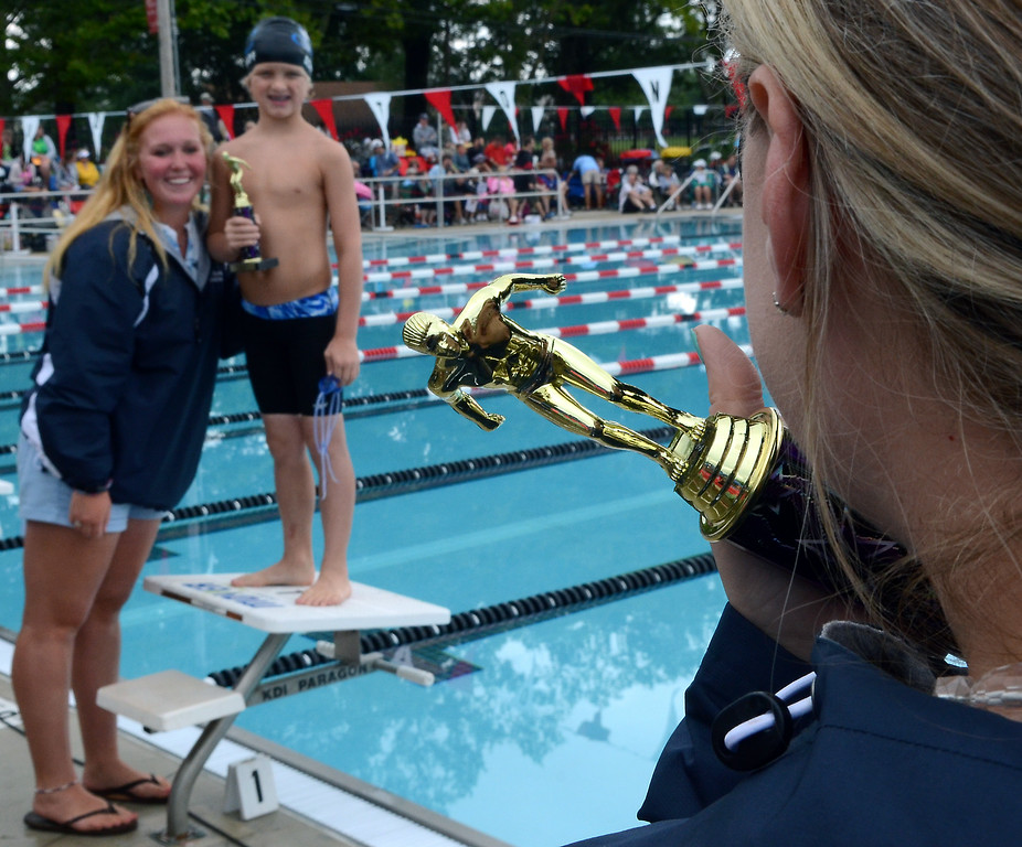 Description of . Fanny Chapman swimmer Aidan Schnapf  and coach Kelly Gavel are seen past a trophy as they pose for a picture during the Bux-Mont Swim League A Championships at the Souderton Community Pool on Saturday August 2,2014. Photo by Mark C Psoras/The Reporter