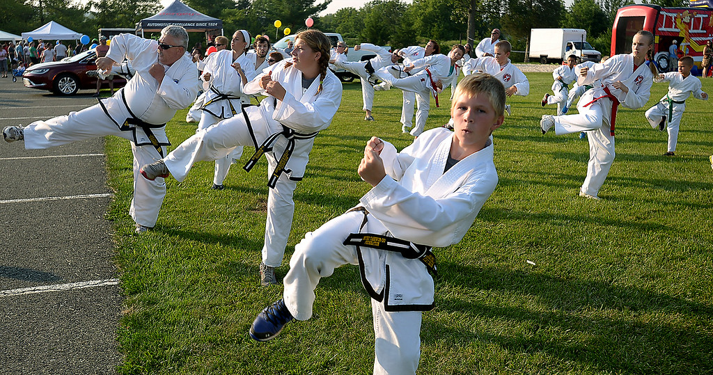 Description of . Kyle Crecher, front, and other students at Mark Cashatt's Tae Kwon-Do School demostrate a series of  kicks, blocks, and punches at the Franconia National Night Out Tuesday, Aug. 5, 2014.Montgomery Media staff photo--Bob Raines
