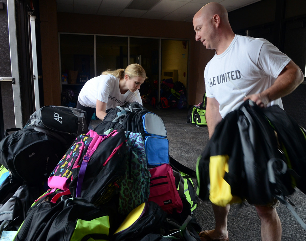 Description of . Stuff the Bus Committee members Gioa Freed and Dave MacFarland stack  backpacks for the North Penn United Way's annual School Supply Drive at Penndale Middle School on Wednesday morning August 6,2014. Photo by Ann Cornell/The Reporter