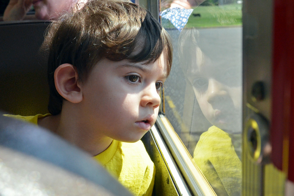 Description of . Kindergartner Hunter Murphy looks out the window during his school bus ride on K Day.     Thursday, August  7. 2014.   Photo by Geoff Patton