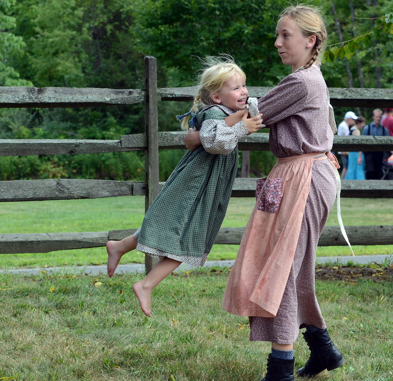 Description of . Magen Perelli ,13, spins around friend Evie Grim ,3, as they play during the Goschenhoppen Historians' 48th annual Folk Festival on Friday August 8,2014. Photo by Mark C Psoras