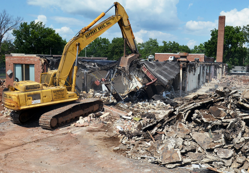 Description of . An operator uses a trackhoe to knock down the former Line Street School at the intersection of Fifth Street and Line Street in Lansdale.  The structure is being razed to make room for a townhome development.    Wednesday,  August 13, 2014.   Photo by Geoff Patton