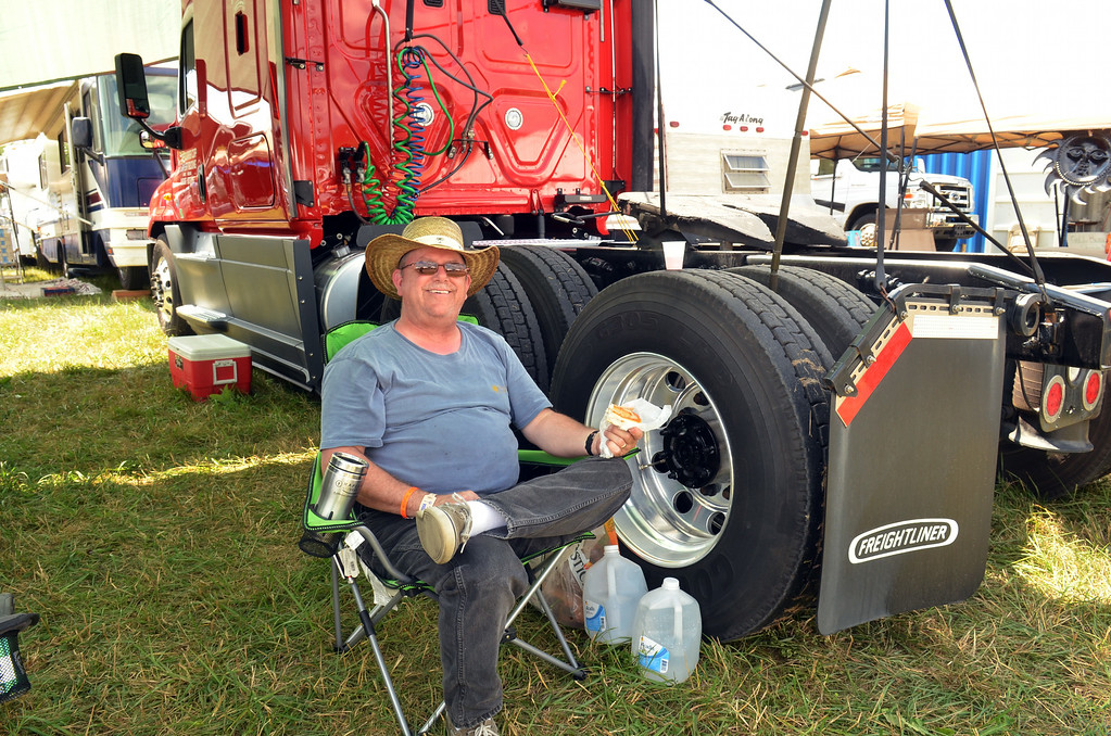 Description of . Using the truck as his camper,  long haul trucker Shelton Domian relaxesat the Philadelphia Folk Festival.   Thursday, August 14, 2014.   Photo by Geoff Patton