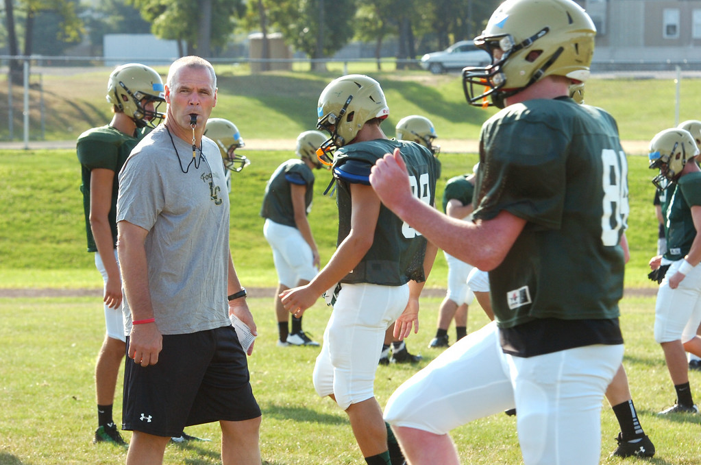 Description of . Coach Tom Kirk with the Lansdale Catholic football team at morning practice.    Monday August 11, 2014.   Photo by Geoff Patton