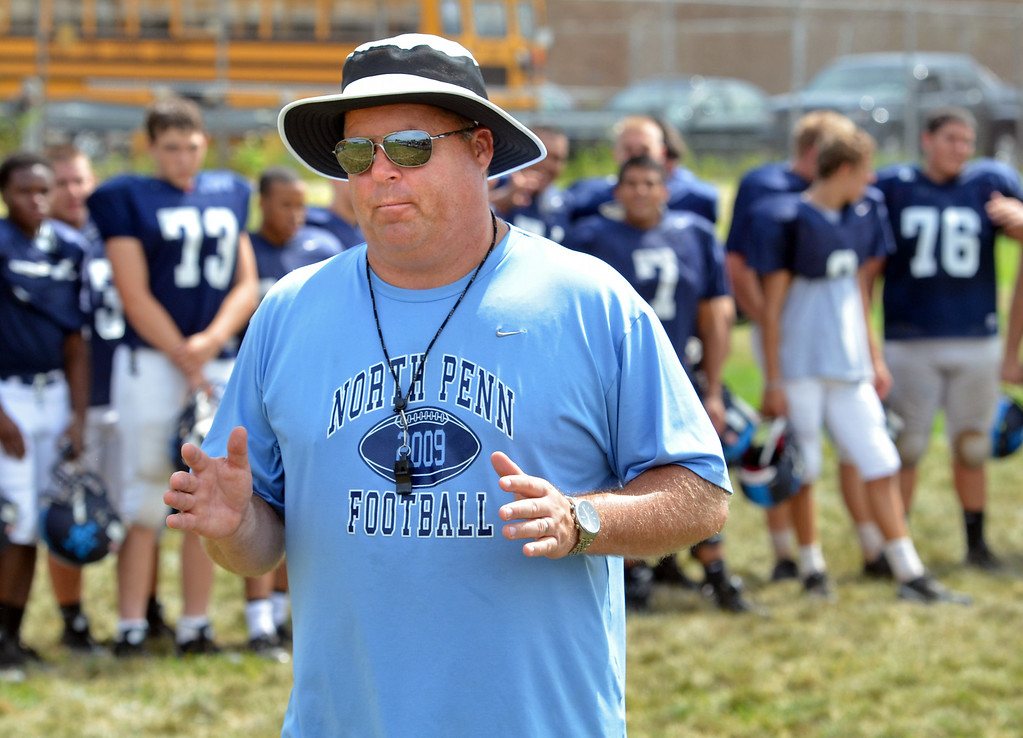 Description of . Coach Dick Beck speaks to North Penn High School players at close of morning practice.   Monday, August 11, 2014.   Photo by Geoff Patton