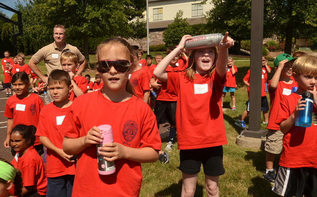 Description of . A  young girl points as a med-evac helicopter lands at Mary, Mother of the Reedemer School during the  Montgomery Township Junior Police Academy.  63 youngsters attended the two-day program which featured demonstrations by the Fire Department of Montgomery Township, a  SWAT team, Montgomery County Bomb Squad, a K-9 unit, and a dive team.   There was also a bicycle safey program, a martial arts demonstration, and a visit by a VMSC Ambulance.    Friday,  August 15, 2014.  photo by Geoff Patton