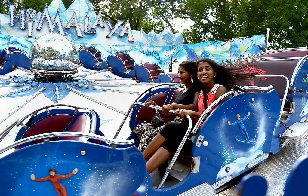 Description of . Michele Thomas, left and Rosilla Edwards ride the Himalaya Melissa Lowrey and her son, Thomas White, 15 months, ride the merry-go-round at the St. Stanilaus Fair Wednesday, Aug. 13, 2014. Montgomery Media staff photo by Bob Raines