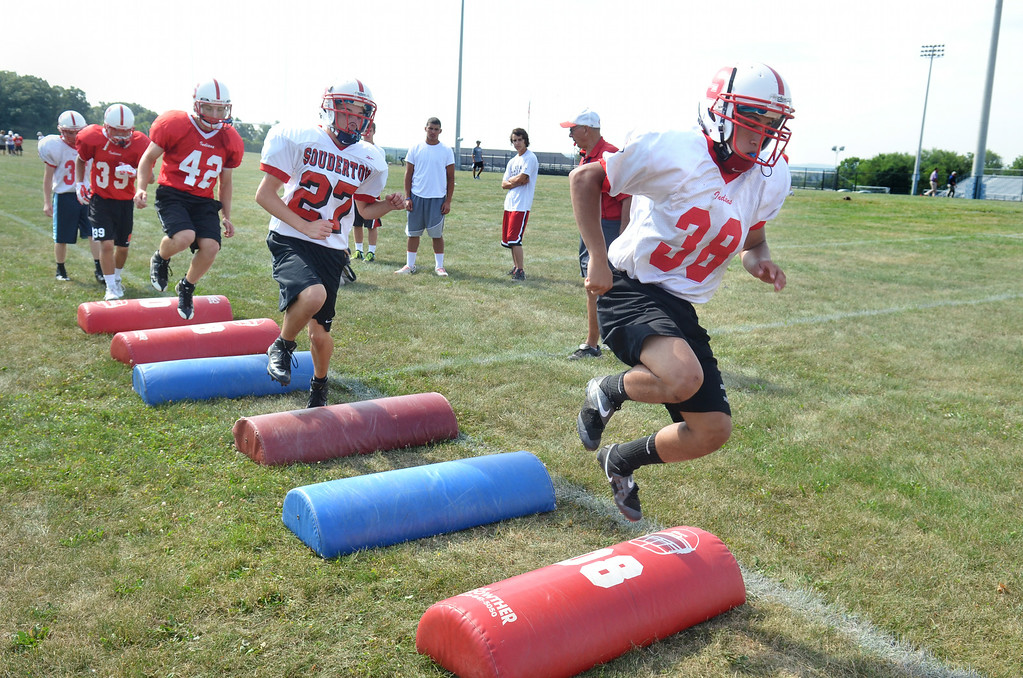 Description of . Members of the Souderton Area High School  football team at morning  practice.    Monday, August 11, 2014.    Photo by Geoff Patton
