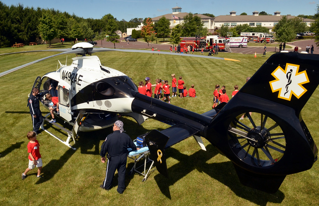 Description of . Youngsters get an up close look at a med-evac helicopter which landed at the  Montgomery Township Junior Police Academy.   63 youngsters attended the two-day program held at Mary, Mother of the Redeemer School  which featured demonstrations by the Fire Department of Montgomery Township,  a SWAT team, Montgomery County Bomb Squad, a K-9 unit, and a dive team.   There was also a bicycle safey program, a martial arts demonstration, and a visit by VMSC ambulance.   Friday, August 15, 2014.  Photo by Geoff Patton