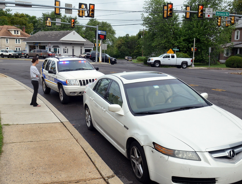 Description of . A motorist involved in a pedestrian accident on Main Street in Souderton waits as an officer in his vehicle writes information.    Wednesday, August 13, 2014.  photo by Geoff Patton