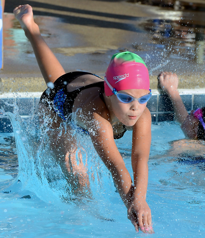 Description of . Harleysville girls 8 and under compete in a free relay event against Hatfield during their BuxMont Swim meet  at the Harleysville Community Pool on Thursday July 17,2014.Photo by Mark C Psoras/The Reporter