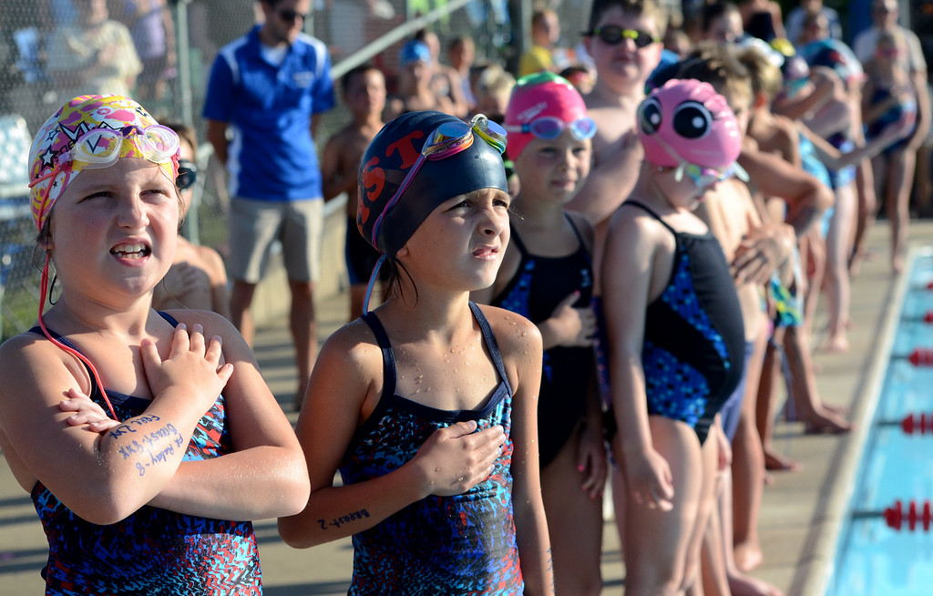 Description of . Hatfield and Harleysville swim team members stand at attention for the singing of the National Anthem before the start of their meet at the Harleysville Community Pool on Thursday July 17,2014.Photo by Mark C Psoras/The Reporter