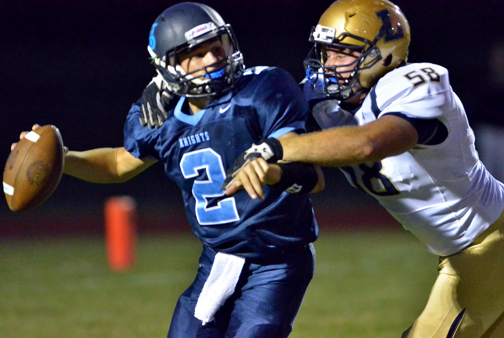 Description of . La Salle defender Keith Wagner ,58, sacks North Penn quarterback Spencer Joner ,2, during first half action of their contest at North Penn High School on Friday August 29,2014. Photo by Mark C Psoras