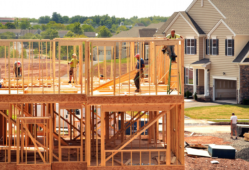 Description of . Workers frame an upper floor of a residence under construction in the Thorndale section of Towamencin Township.   Tuesday,  August 26, 2004.   Photo by Geoff Patton