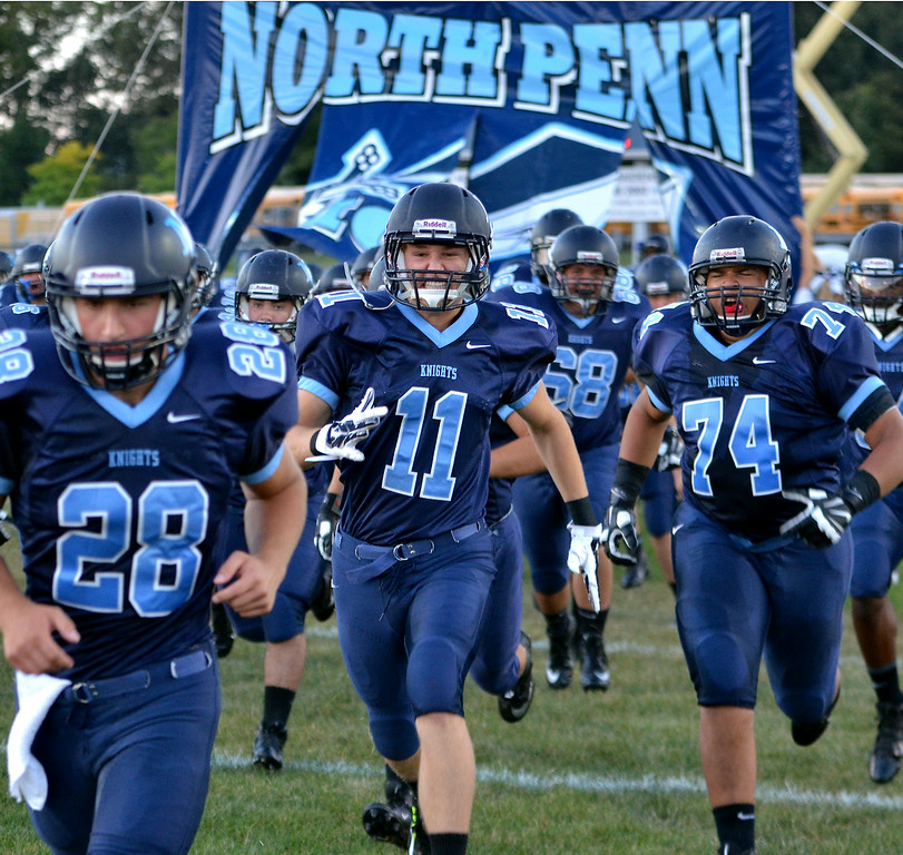 Description of . The North Penn Knights Football team take the field before their contest against  La Salle at North Penn High School on Friday August 29,2014. Photo by Mark C Psoras