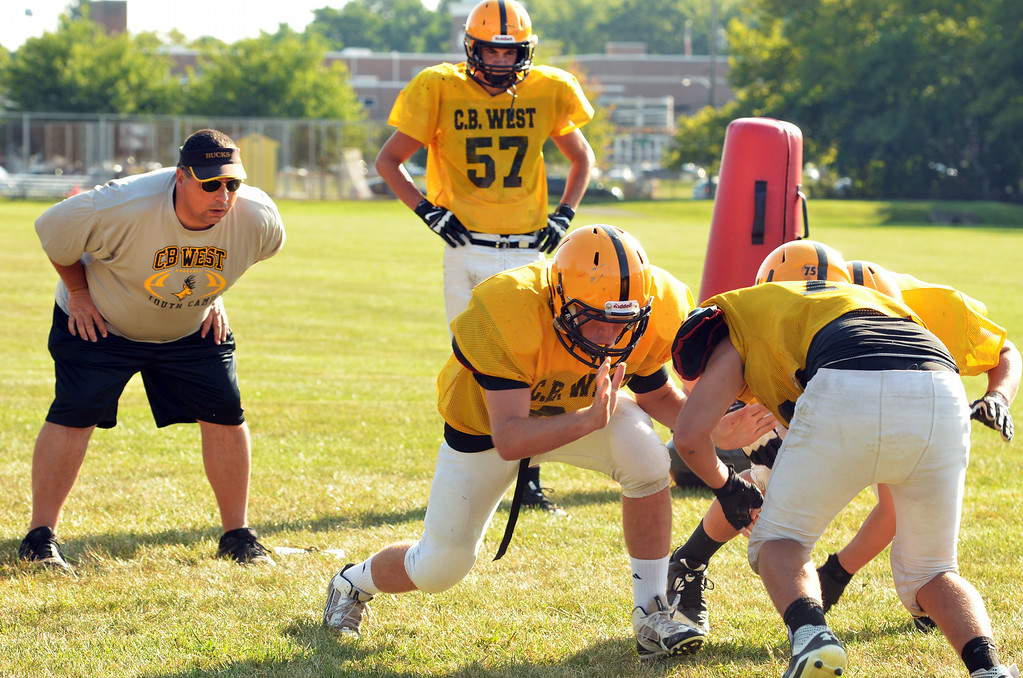 Description of . Central Bucks West football players at a morning practice.   At left is coach Brian Hensel.   Tuesday,  August 19, 2014.   Photo by Geoff Patton