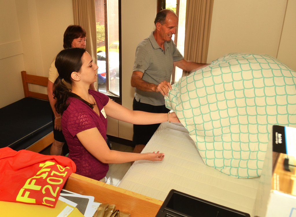 Description of . Gerry Fleury makes the bed in residence hall for his daughter Eileen in a residence hall on move-in day at Gwynedd Mercy University.   At left is Mary Fleury.  Thursday, August 21, 2014.   Photo by Geoff Patton