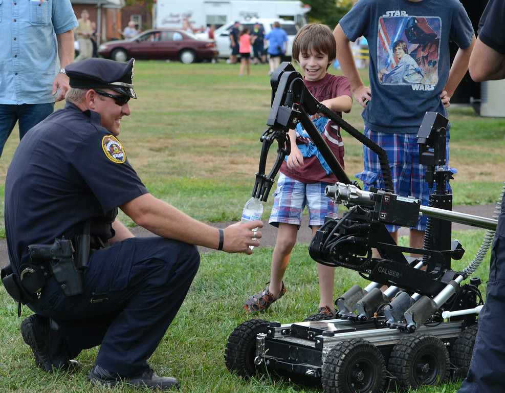 Description of . Souderton Police officer Jeff Lukens holds a bottle as the Montgomery County Sheriff's Department Bomb Squad gives a demonstration with one of their robots during the Souderton and Telford Police Departments Community Night Out on Tuesday evening August 19,2014. Photo by Mark C Psoras/The Reporter