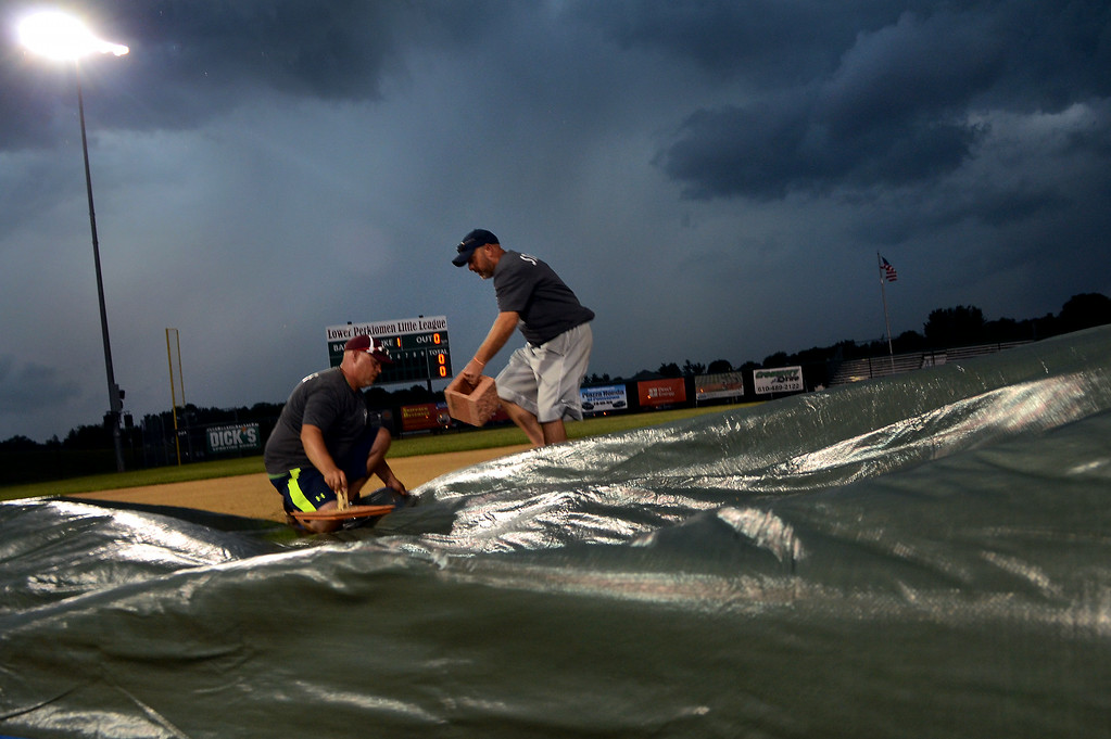 Description of . Members of the grounds crew secure tarps over the mound on the ballfield with heavy thunder storms canceling the Pennsylvania Little League State Tournament evening game at Palmer Park on Wednesday July 23,2014.Photo by Mark C Psoras/The Reporter