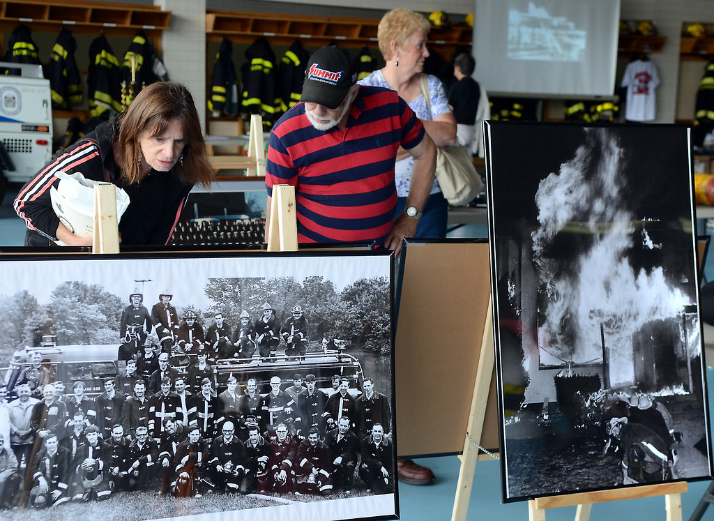 Description of . Displays of old photos and fire equipment are inspected for the  Fairmount Fire Company 125th Anniversary festivities during the Lansdale Founders Day celebration on Saturday August 23,2014. Photo by Mark C Psoras/The Reporter