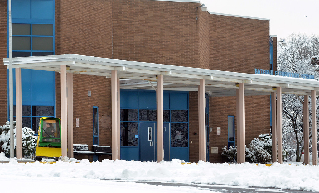 Description of . A worker clears snow near the front door of Hatfield Elementary School. (The Reporter/Geoff Patton)