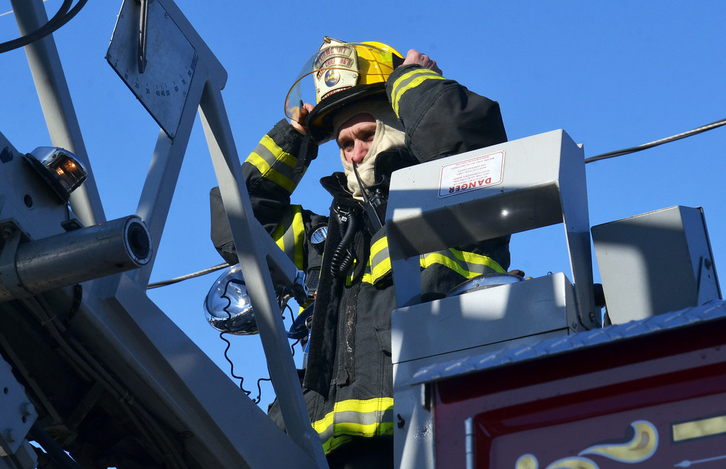 Description of . A ladder operator adjusts his headgear at scene of house fire on Forty Foot Road in Hatfield Township.   Thursday, Janury 23, 2014.  Photo by Geoff Patton