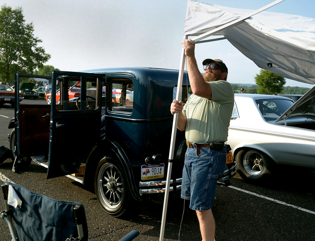 Description of . Rich Shirley sets up a tent behind his 1928 Dodge at the Franconia National Night Out Tuesday, Aug. 5, 2014.Montgomery Media staff photo--Bob Raines