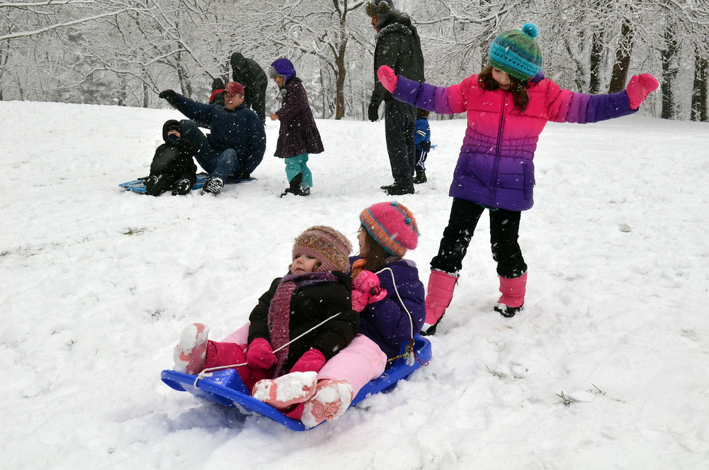Description of . Emma, left, and Marie O'Donnell get a push from their sister Alise at Whites Road Park in Lansdale.    (The Reporter/Geoff Patton)