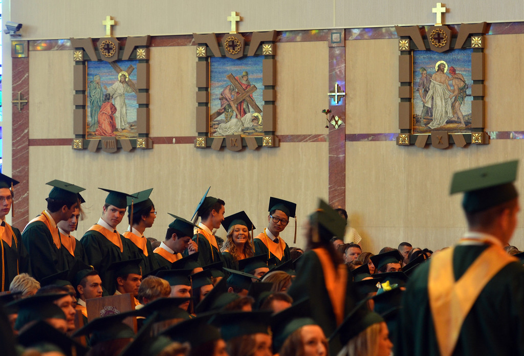 Description of . Seniors stand as diplomas are conferred at the Lansdale Catholic high school commencement ceremony.   Tuesday, June 3, 2014.  Photo by Geoff Patton