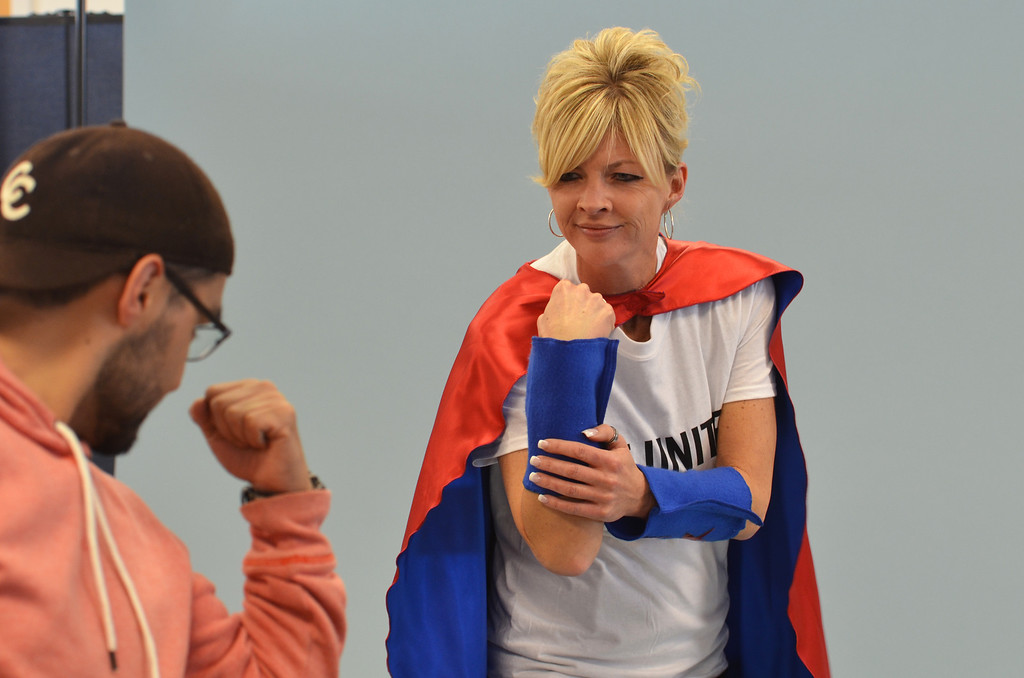 Description of . Photographer Marco Calderon encourages Robyn Garis to project strength during a shoot for the North Penn United Way's third annual Superheroes United for Kids event.   Finished photographs are used in promotion and will be  displayed during the event in April.   Friday, January 24, 2014.  Photo by Geoff Patton