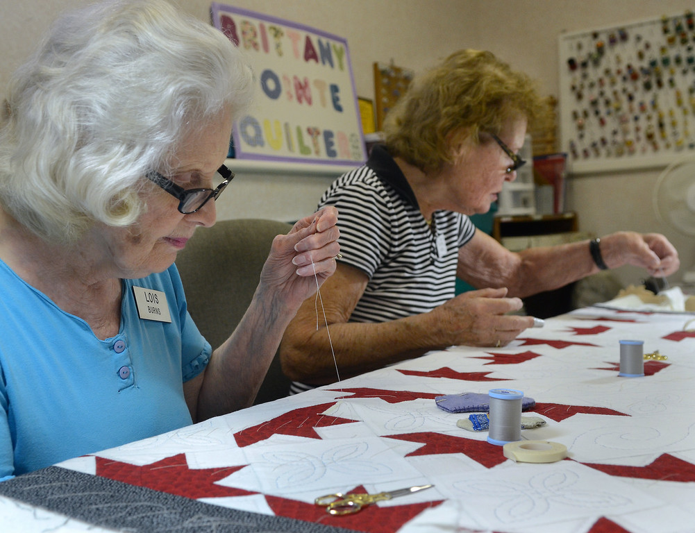 Description of . Brittany Pointe Quilter Lois Burns (L) and members work on quilts for this years holiday season at Brittany Pointe Estates in Upper Gwynedd on Tuesday August 8,2014. Photo by Mark C Psoras/The Reporter
