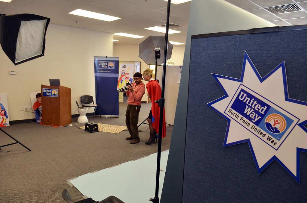 Description of . Photographer Marco Calderon at work with Robyn Garis during a shoot for the North Penn United Way's third annual Superheroes United for Kids event.   Finished photographs are used in promotion and will be  displayed during the event in April.   Friday, January 24, 2014.  Photo by Geoff Patton