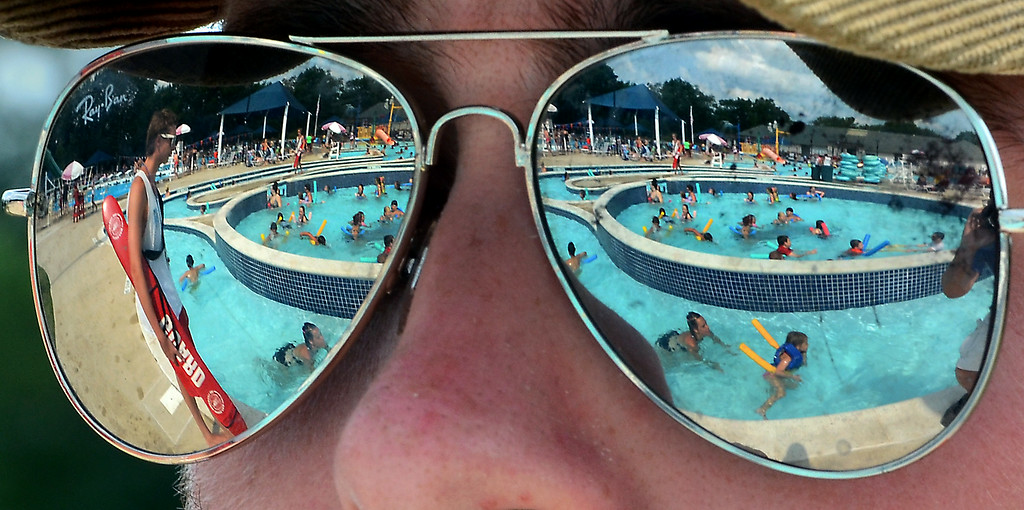 Description of . A packed crowd at the Hatfield Aquatic Center is reflected in the sunglasses of Pool Deck manager Tim McCann on a hot and steamy Wednesday July 23,2014.Photo by Mark C Psoras/The Reporter