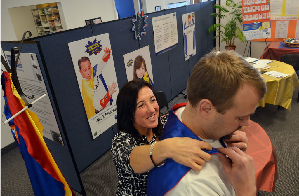 Description of . Christy Holland helps Josh Rennells get ready for a photo shoot for the North Penn United Way's third annual Superheroes United for Kids event.   Finished photographs are used in promotion and will be  displayed during the event in April.   Friday, January 24, 2014.  Photo by Geoff Patton