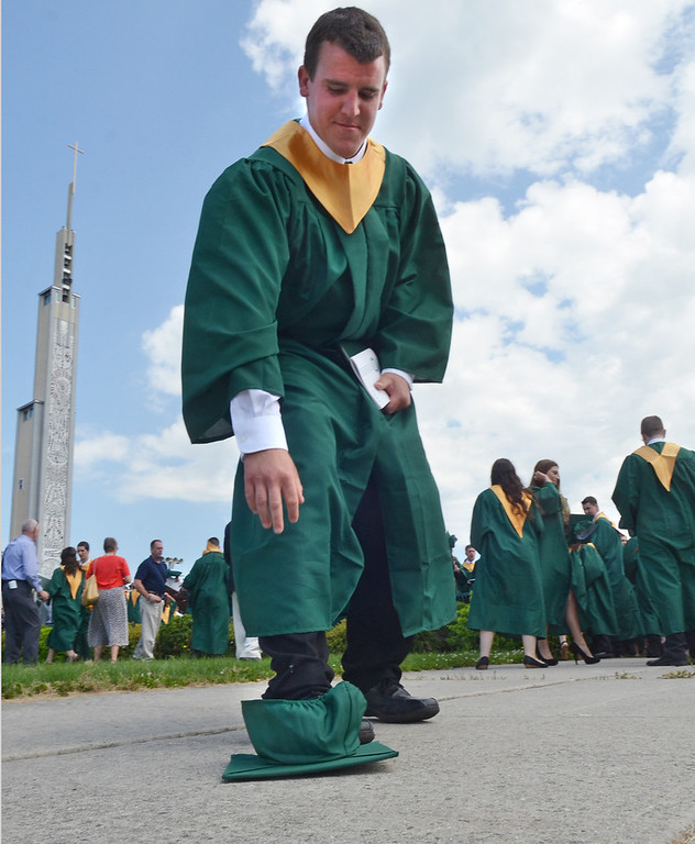 Description of . Graduate Jake Robb picks up the cap he tossed following the Lansdale Catholic high school commencement ceremony at the Shrine of Czestochowa.   Tuesday, June 3, 2013.    Photo by Geoff Patton
