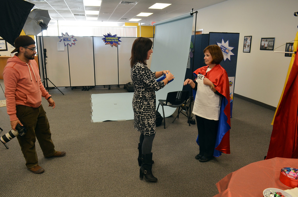 Description of . Christy Holland, center, helps Debbie Levin from Montgomery County Community College prepare for a photo shoot for the North Penn United Way's third annual Superheroes United for Kids event.   Finished photographs are used in promotion and will be  displayed during the event in April.   Friday, January 24, 2014.  Photo by Geoff Patton