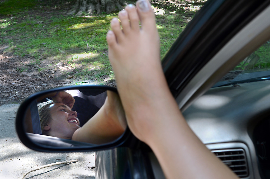 Description of . Cheltenham High School student Rachel Davis is reflected in the driver side mirror of her car as she kicks back with a friend parked at the Curtis Arboretum on a hot and sunny Tuesday afternoon August 5,2014. Photo by Mark C Psoras/The Reporter