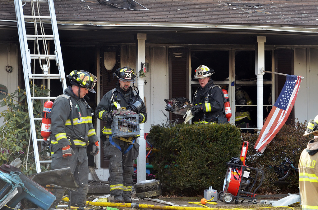 Description of . Firefighters clear damaged items from inside a home on Adams Avenue in Hatfield Township  following fire.   Thursdsay, March 27, 2014.   Photo by Geoff Patton