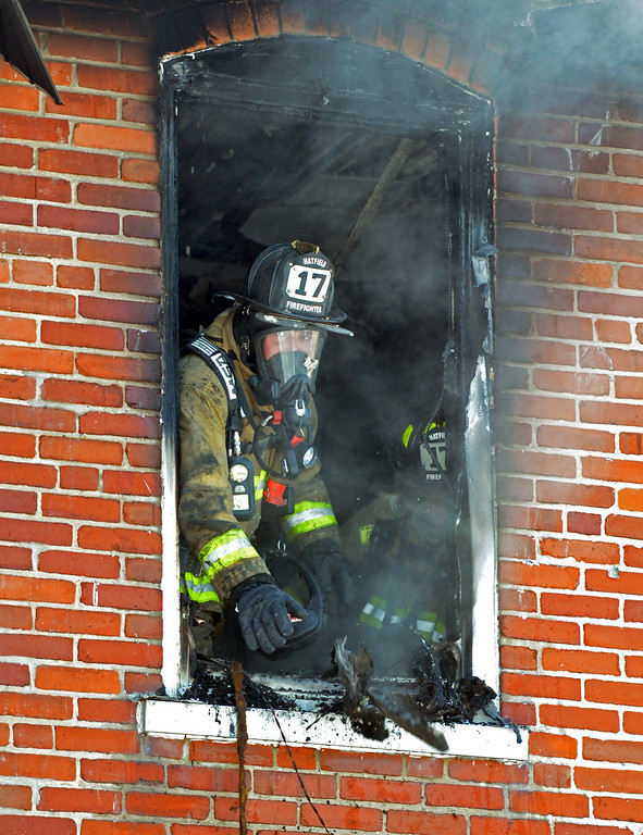 Description of . A firefighter removes debris from second floor of home  on Forty Foot Road in Hatfield Township following a fire.   Thursday, January 23, 2014.  Photo by Geoff Patton