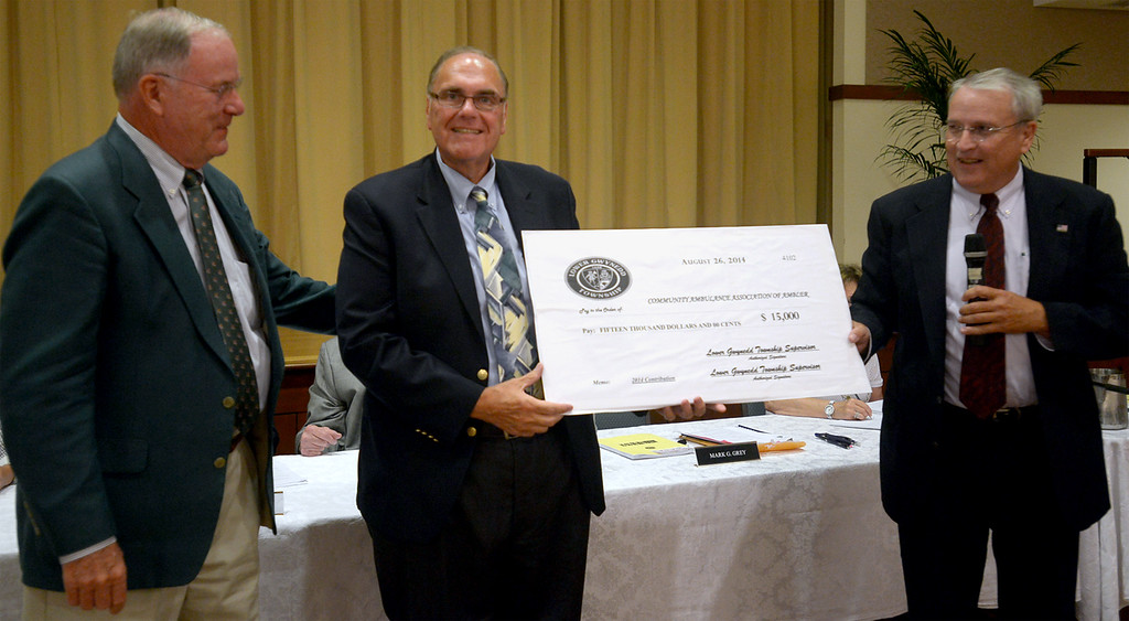 Description of . Lower Gwynedd Supervisors Richard Booth, left, and Mark Grey, right, present a check to Community Ambulance Association of Ambler Executive Director David Fleming for $15,000. during a board of supervisors meeting held at Foulkeways Tuesday, Aug. 25, 2014. Montgomery Media staff photo by Bob Raines