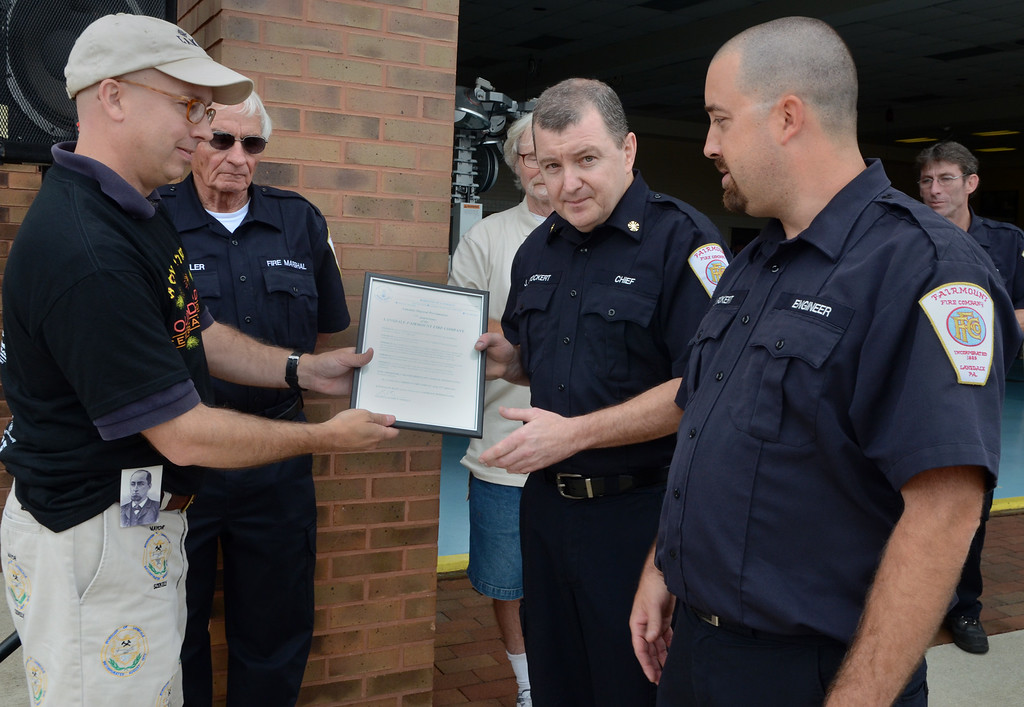 Description of . Lansdale Mayor Andy Szekely ,L, presents a proclamation to Fairmount Fire Company Chief Joe Stockert (center) President Ian Fickert (R) and Fire Marshall Jay Davelar (2nd from L) in recognition of the companies 125th Anniversary during the Lansdale Founders Day celebration on Saturday August 23,2014. Photo by Mark C Psoras/The Reporter