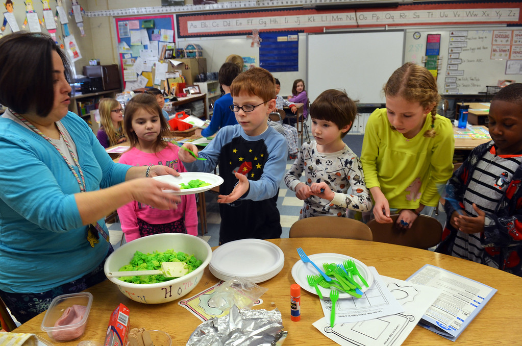Description of . Teacher Danielle Scheer serves green eggs and ham to her first grade students at Montgomery Elementary School.  The colorful snack  was served as part of Reading Week activity held annually to celebrate Dr. Seuss's birthday.   Friday, March 7, 2014.   Photo by Geoff Patton