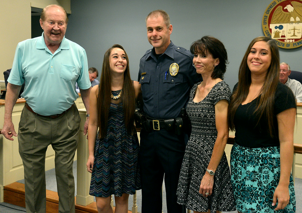 Description of . Upper Gwynedd Police Sgt. Steve Gillen, center, stands with, from left, Commissioner Eugene Ziemba, his daughter, Mackenzie, his wife, June, and his daughter,  Melissa as he is recognized for 25 years of service to the township Monday, Aug. 25, 2014.