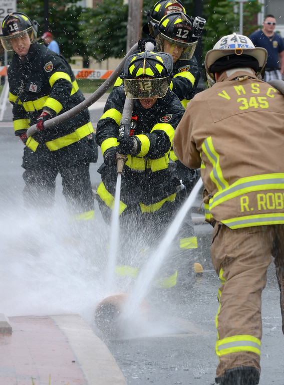 Description of . Colmar Fire Company members and VMSC compete in a water battle demonstration for the Fairmount Fire Company 125th Anniversary festivities during the Lansdale Founders Day celebration on Saturday August 23,2014. Photo by Mark C Psoras/The Reporter
